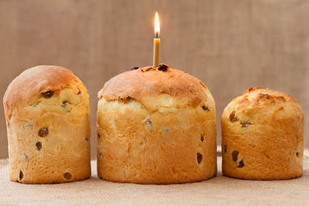 easter candle is burning: Baked traditional religious easter cake also called kulich with burning candle on vintage textile background