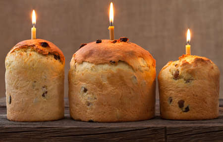 easter candle is burning: Baked traditional religious easter holiday sweet cake also called kulich with raisins and burning candle on vintage textile background