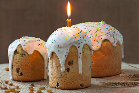 easter candle is burning: Traditional homemade ukrainian culture easter cake called kulich sweet bread with one burning candle and icing on rustic textile background