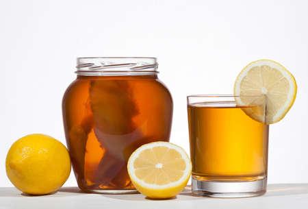 Kombucha super food pro biotic beverage in glass with lemon on white background