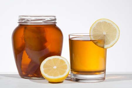 Kombucha superfood pro biotic beverage in glass with lemon on white background
