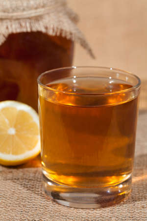 Kombucha superfood pro biotic tea fungus beverage in glass with lemon on white background Archivio Fotografico