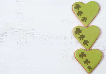 Patricks day green cookies with clover on vintage white background top view photo