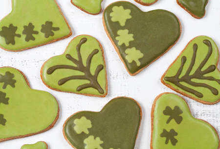 Patricks day green cookies with sugar icing clover on vintage white background top view photo