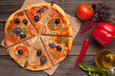 Sliced italian pizza margherita with tomatoes, olives and basil on rustic background top view photo
