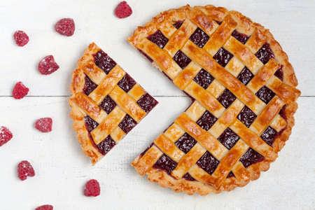 白いテーブルに新鮮な砂糖ラズベリーとラズベリーのパイをスライス 写真素材