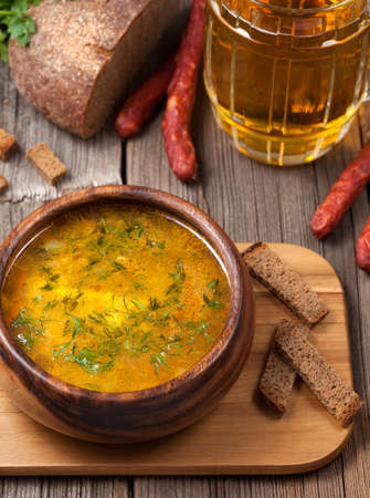 Traditional bavarian beer soup with sausage croutons parsley and beer on vintage background photo