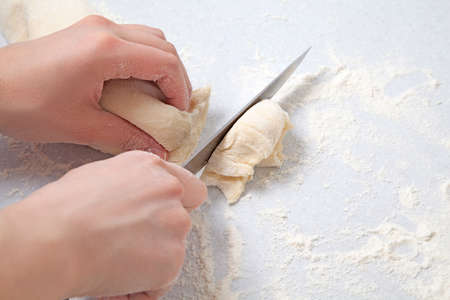 Womans hands cuttingt dough on a table with flour photo