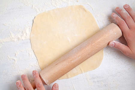 knead: Womans hands knead dough on a table with rolling pin