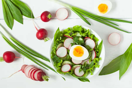 Healthy clean eating vegetarian salad with radish, onion, green salad, onion and parsley on white background