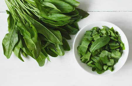 Raw fresh sorrel plant leafs in white bowl on rustic background. Nutrition full of vitamines. Stockfoto