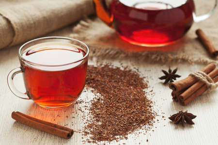 rooibos tea: Traditional healthy red african rooibos tea in glass cup with spices on vintage table background