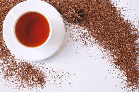 Top view of red traditional African rooibos tea in white cup with star anise on white vintage table background