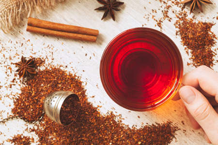 Unrecognizable man holding cup of healthy organic african rooibos tea with spices on vintage wooden background