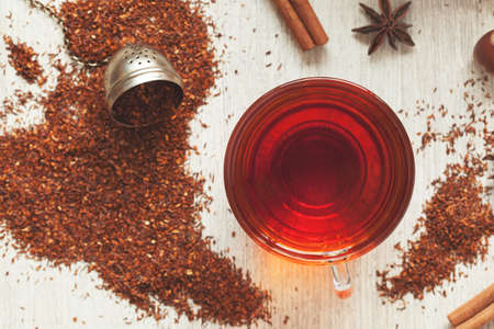 Glass cup of tasty organic herbal rooibos red tea with spices on vintage table background. Top view Stock Photo