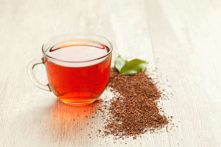 Cup of traditional tasty herbal rooibos tea on vintage wooden table