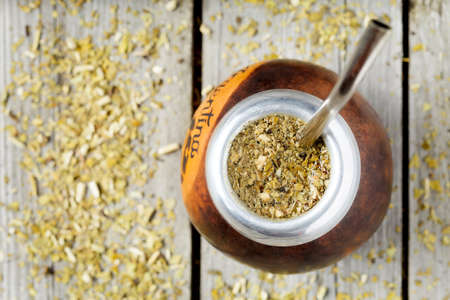 mate infusion: Traditional Argentina yerba mate tea beverage in calabash and bombilla in rustic style on vintage wooden background Stock Photo