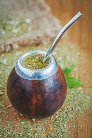 Latin traditional yerba mate tea in calabash with bombilla on wooden table background with green leaves