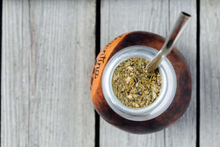 Healthy yerba mate tea in kalabash with bombilla in rustic style on vintage wooden background