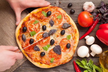 Cutting with knife italian pizza margherita with tomatoes, olives and basil top view photo