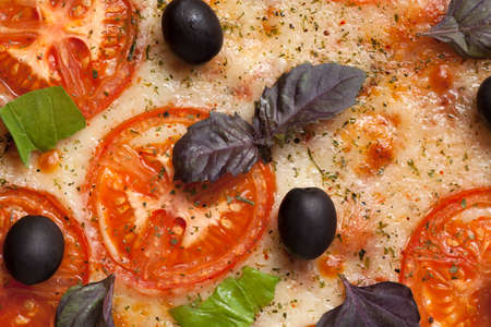 Traditional italian pizza margherita with tomatoes, pepper, olives and basil close up photo