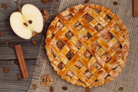 Apple pie with raisins, nuts and cinnamon on vintage wooden background texture. Top view