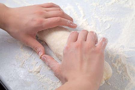 knead: Womans hands knead dough on a table with flour