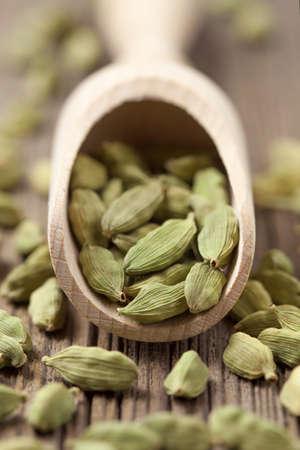 �pices: Les graines de cardamome verte SuperFood ayurveda �pice dans une pelle en bois sur fond mill�sime Banque d'images