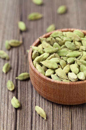 aroma bowl: Green cardamom ayurveda asian aroma spice in a wooden bowl on vintage background Stock Photo