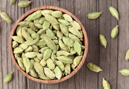 aroma bowl: Green cardamom ayurveda plant aroma spice in a wooden bowl on vintage background Stock Photo