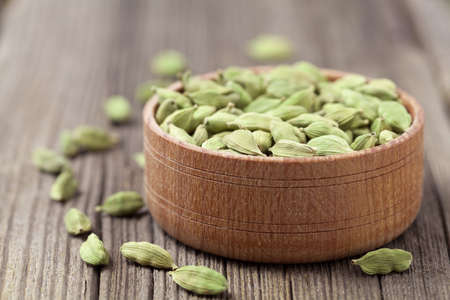aroma bowl: Green cardamom super food ayurveda asian aroma spice flavour in a wooden bowl on vintage background