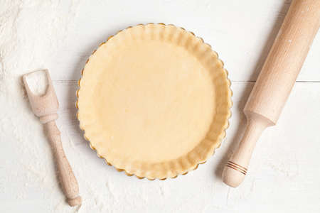 Homemade tart pie preparation, dough with yeast and rolling pin on white rustic kitchen table