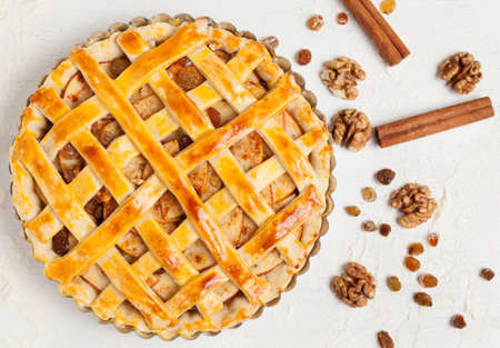 Uncooked homemade rustic apple pie preparation greased with egg yolk on white kitchen background