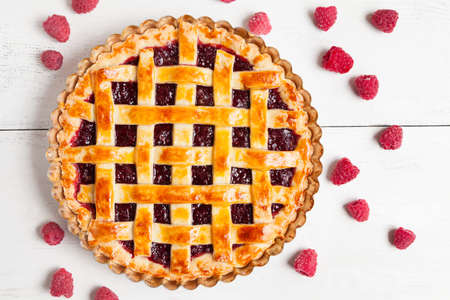 Tasty homemade raw raspberry pie greased with egg yolk with jam on white rustic kithen table background
