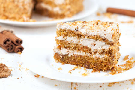 Piece of sliced gourmet carrot cake dessert with sweet cream and walnut on white plate photo