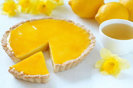 Delicious homemade lemon tart pie with green tea on rustic white table