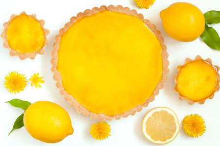 Tasty homemade backed lemon tart pie dessert with narcissus flowers on white rustic background table