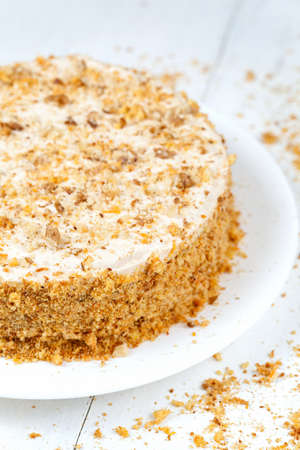 Tasty carrot cake with pastry cream and walnut crumbs on white background photo