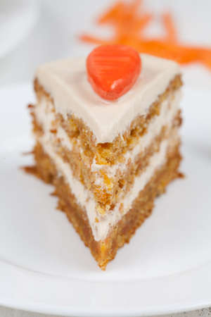 Tasty piece of homemade carrot easter cake with little orange carrot on white dish photo