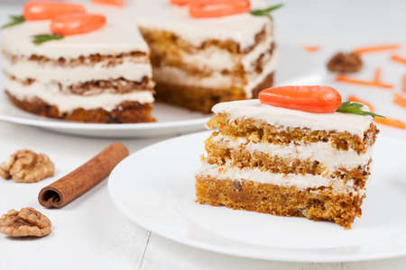 Delicious slice of carrot sponge cake with icing cream and little orange carrots on white background Stockfoto