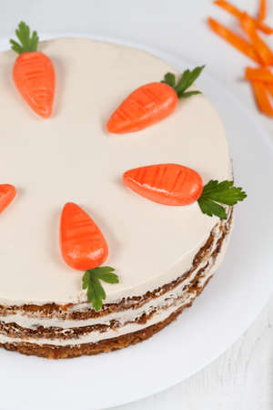 Easter cake with little carrots on white dish on white background photo
