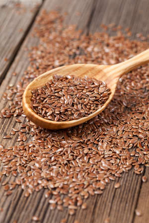 brown flax: Healthy little brown flax seeds super foods  in wooden spoon. Organic vegetarian nutrition close up. Stock Photo