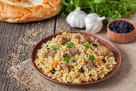 아랍어 전통적인 소박한 쌀 음식 필라프 튀긴 된 고기, 양파, 당근, 마늘 목조 배경 테이블에 요리