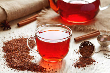 Cup of healthy traditional herbal rooibos red beverage tea with spices on vintage wooden table Foto de archivo