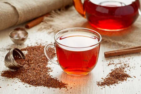 Healthy rooibus tea traditional south africa antioxidant beverage with spices on vintage wooden table in rustic style Stock Photo