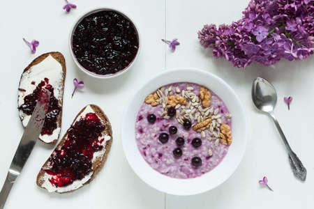 Clean eating diet healthy breakfast. Oatmeal porridge muesli with nuts, sunflower seeds, berries and berry jam. Two toasts with butter and jam. Served on white kitchen table background with lilac flowers. Rustic style, natural light.