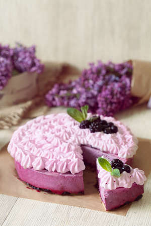 homemade style: Berry purple souffle cake. Traditional delicious homemade baked sweet decorated with blackberry and whipped cream. Rustic style, natural light.