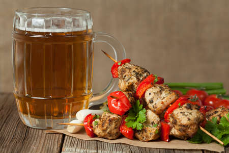 Gourmet chiken kebab skewer barbecue meat on bamboo sticks with glass of beer on rustic wooden table background. Rustic style, natural light.