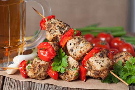 대나무 지팡이에 야채, 녹색 양파와 맥주와 함께 맛있는 전통 닭 또는 칠면조 케밥 꼬치 바베큐 고기. 부엌 테이블 배경에 재직했습니다. 소박한 스타 스톡 콘텐츠