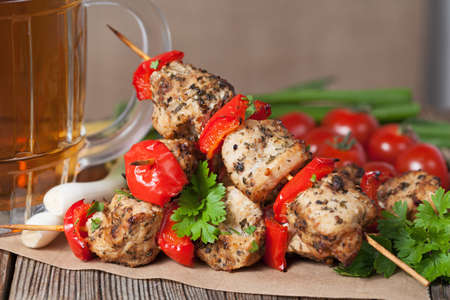 skewer: Delicious traditional chicken or turkey kebab skewer barbecue meat with vegetables, green onion and beer on bamboo sticks. Served on kitchen table background. Rustic style, natural light. Stock Photo